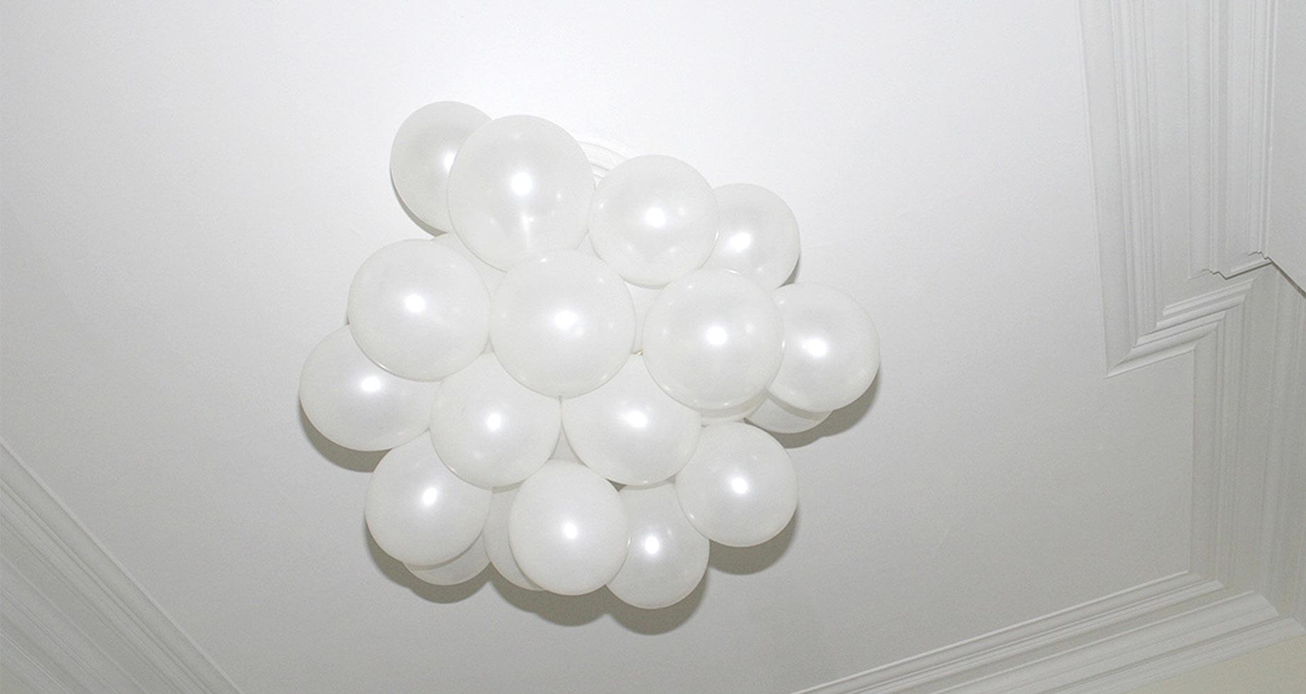 Weiße Ballons schweben an Stuckdecke