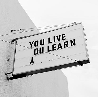 Außentafel mit Spruch You live, you learn