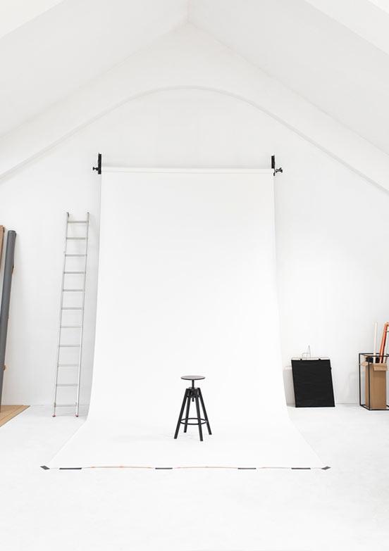 Fotoatelier mit ausgerolltem weißen Hintergrund und Leiter daneben